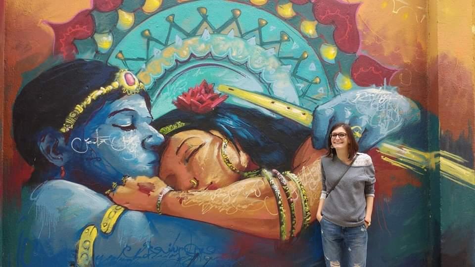 ragazza Expat che si è trasferita in Spagna per studiare sorride davanti al murales