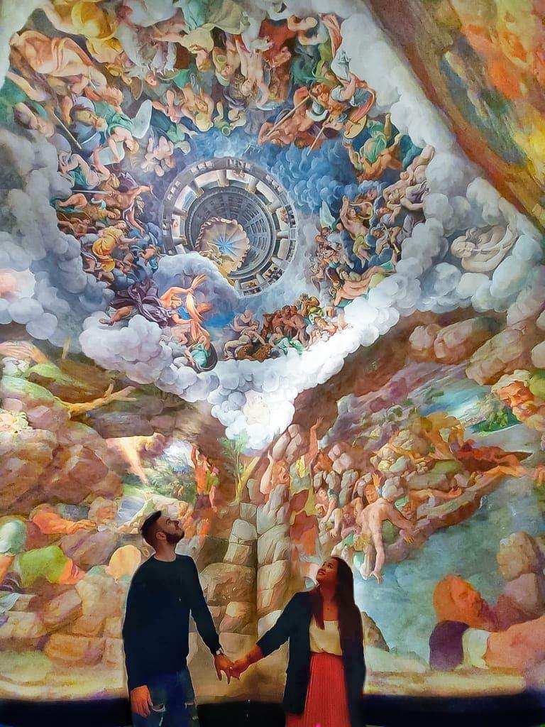 coppia guarda meravigliata la bellissima sala dei giganti all'interno del Palazzo Te a Mantova
