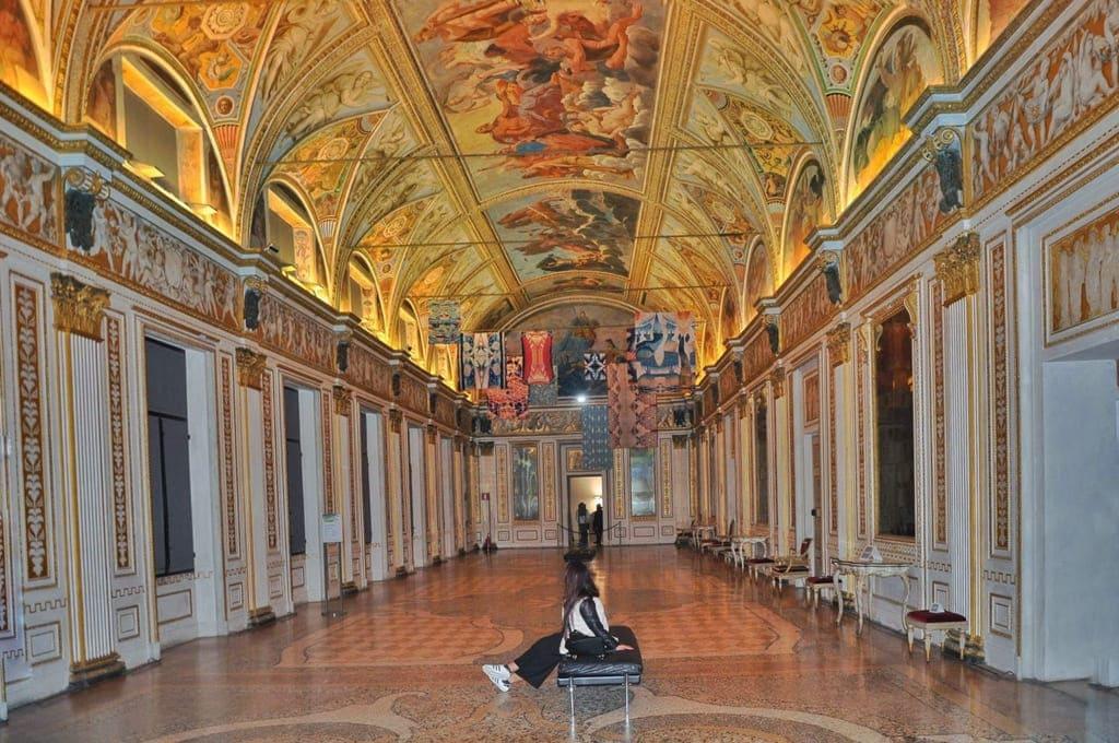 Ragazza ammira l'arte nella sala degli specchi dentro al Palazzo Ducale di Mantova