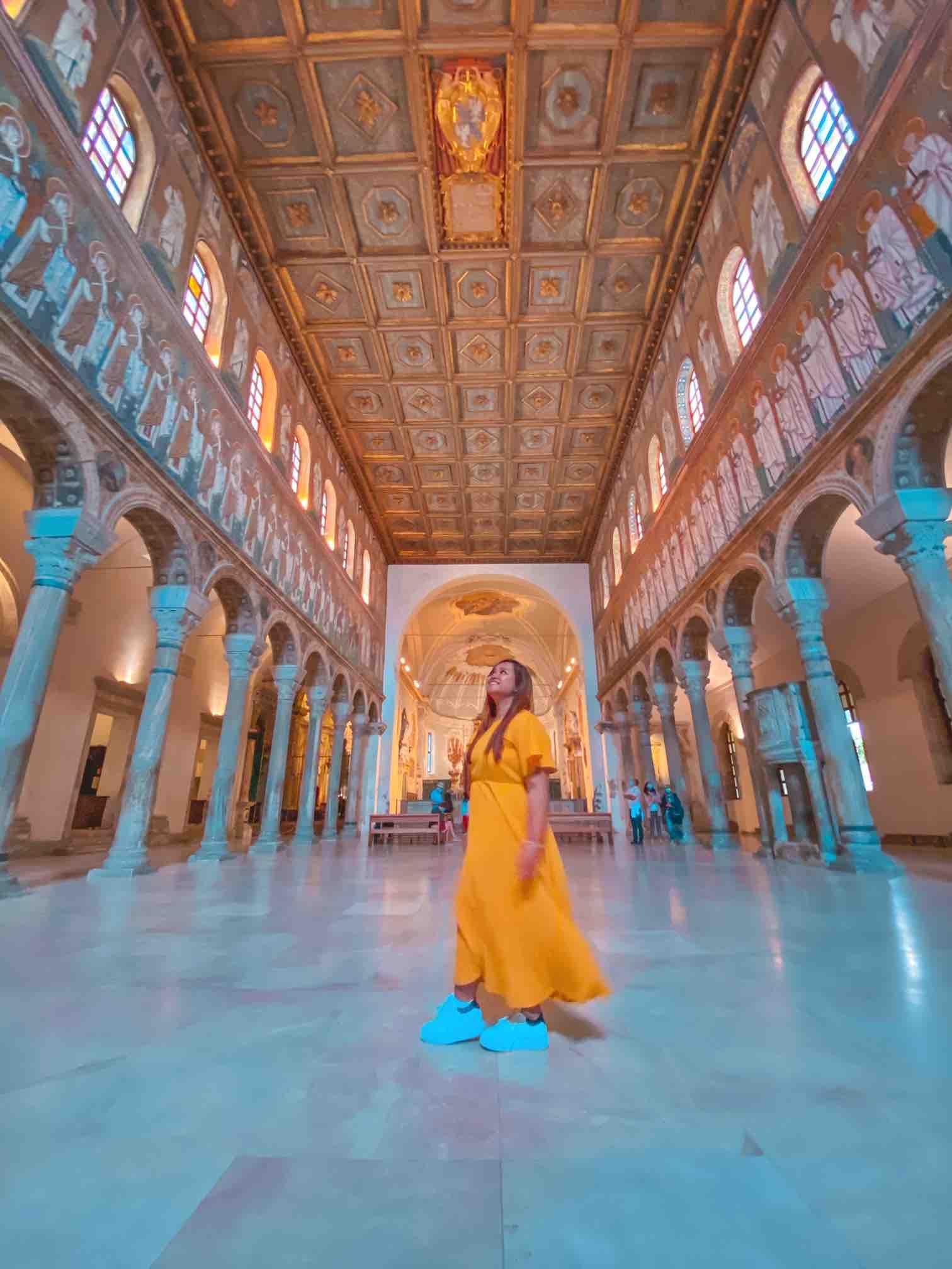 ragazza ammira la Basilica di Sant'Apollinare Nuovo, un'attrazione da vedere in due giorni a Ravenna
