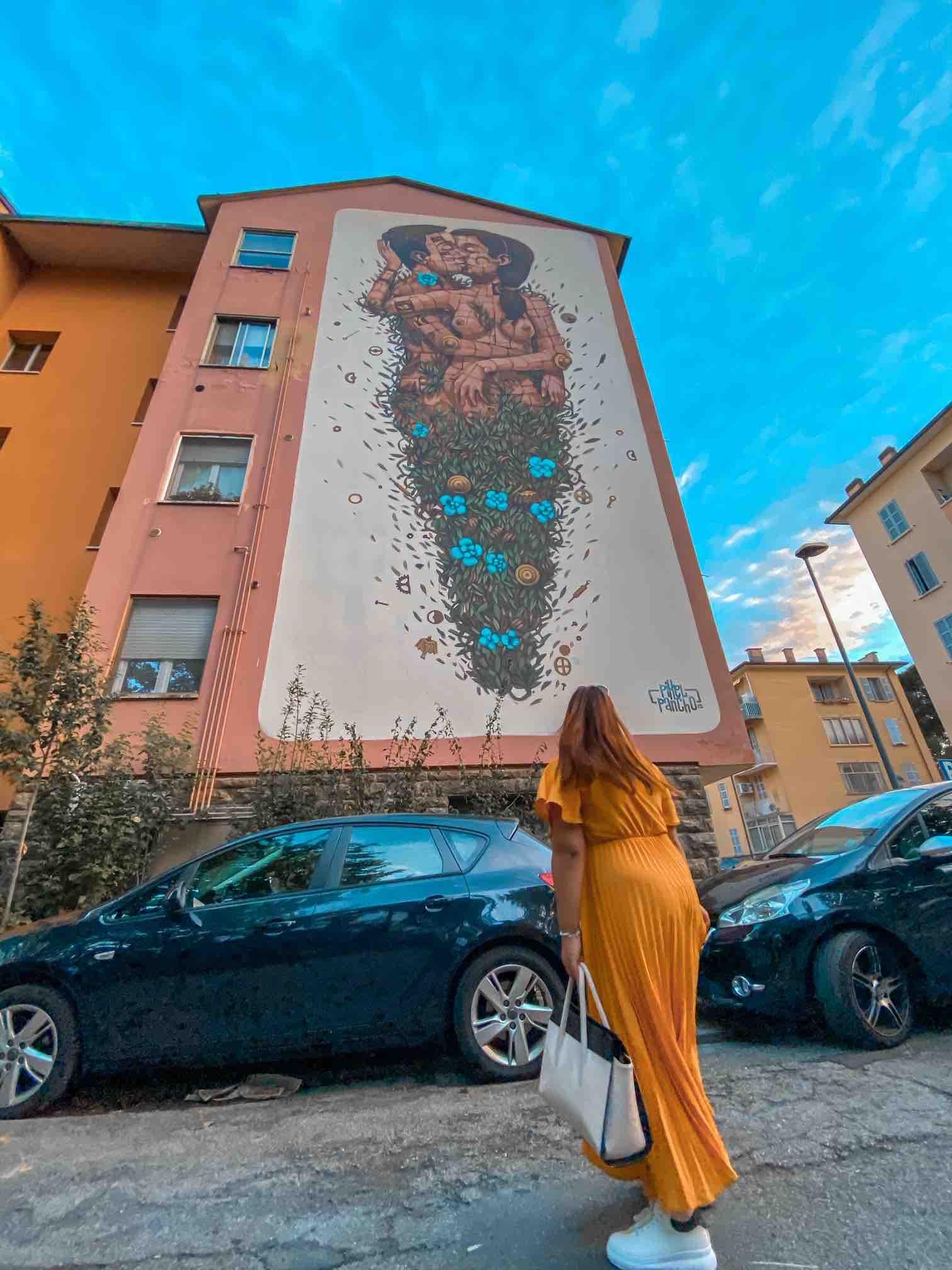 ragazza osserva il murales degli innamorati che si baciano a Ravenna da vedere in un viaggio di tre giorni