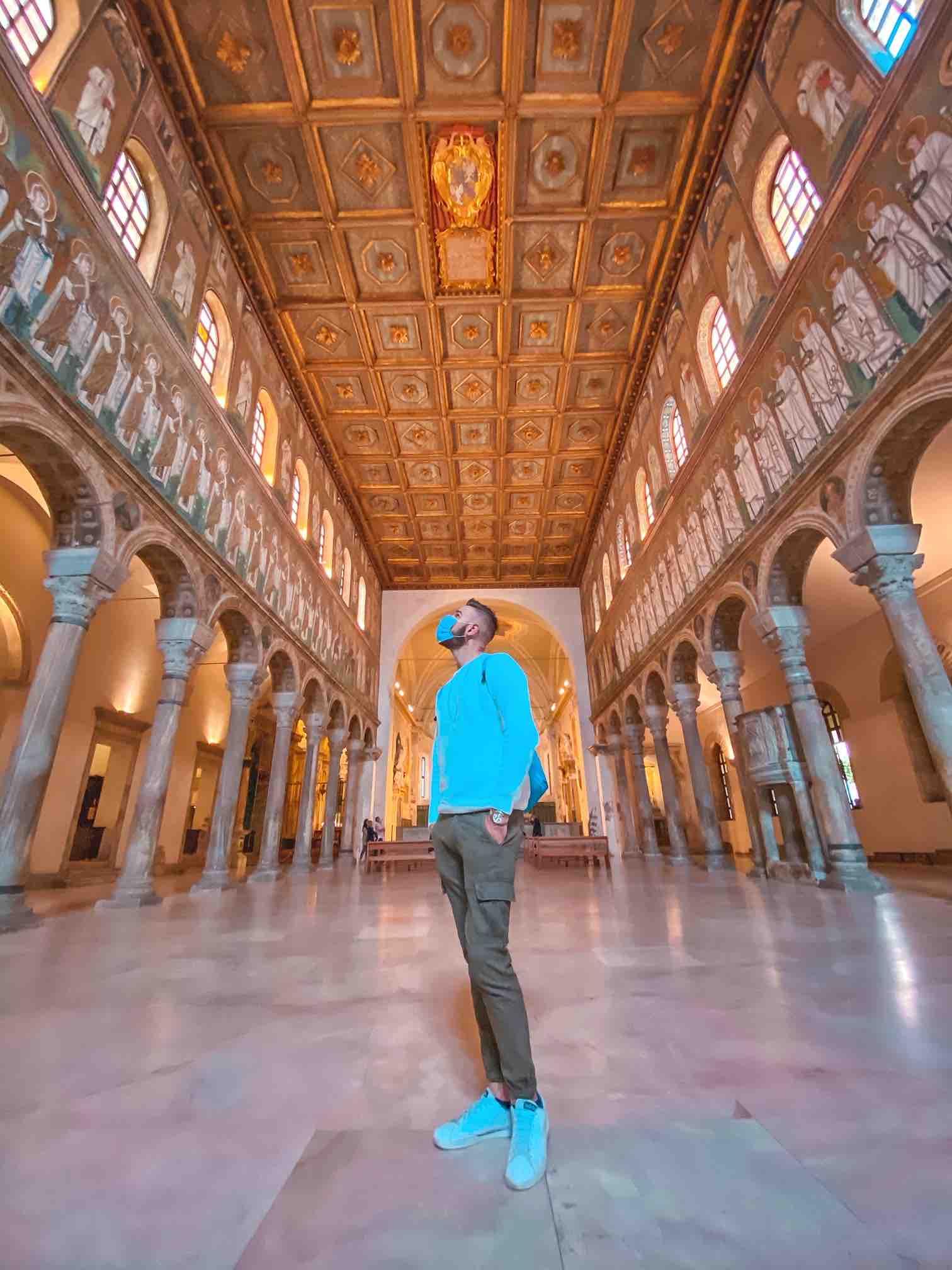 ragazzo ammira i mosaici dentro Sant'Apollinare nuovo, attrazione da vedere a Ravenna in due giorni