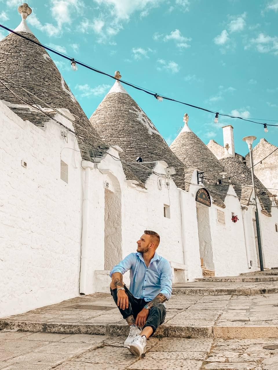 ragazzo seduto via Alberobello quinto giorno itinerario una settimana Puglia