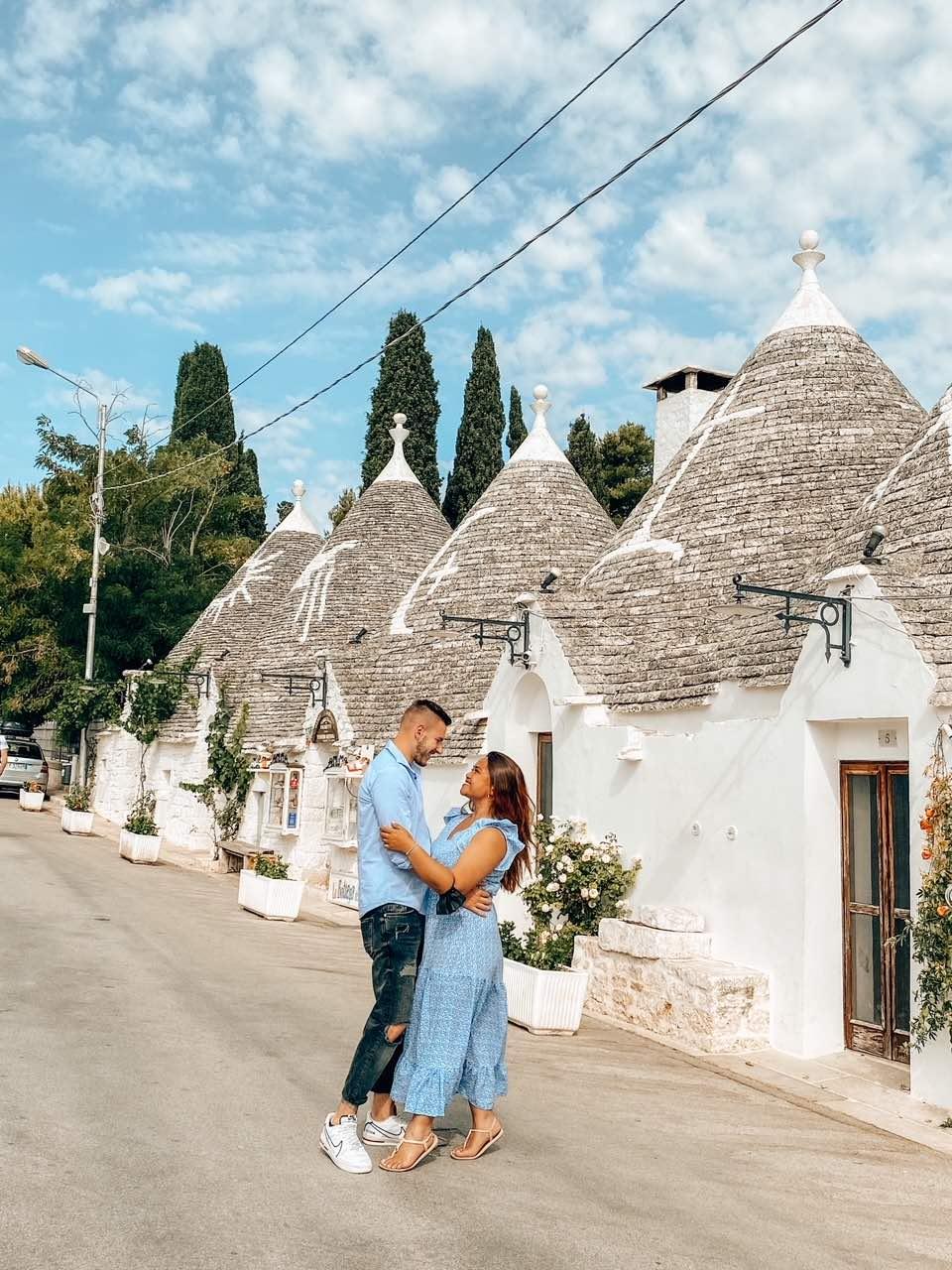 Innamorati si guardano in una via piena di trulli ad Alberobello in Puglia