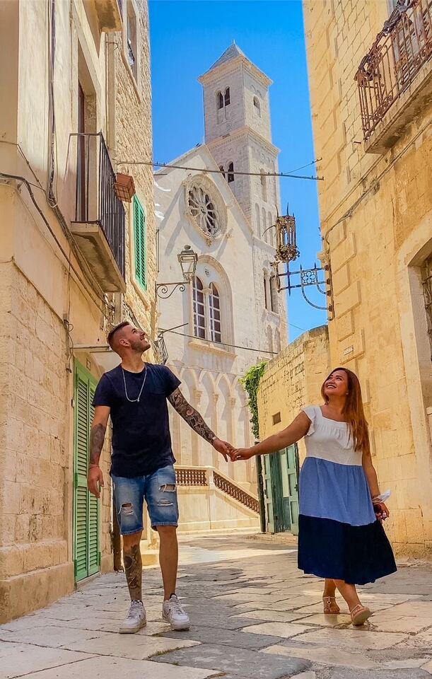 coppia cammina in un bellissimo vicolo di Giovinazzo davanti alla cattedrale di Santa Maria Assunta