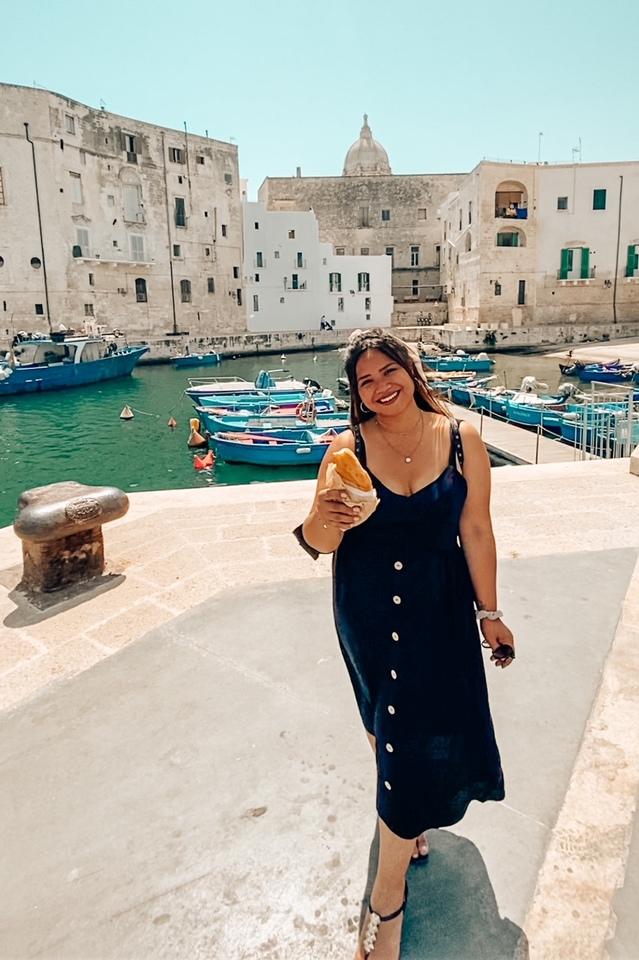 ragazza sorridente che mangia il panzarotto pugliese nel bellissimo porto antico di Monopoli