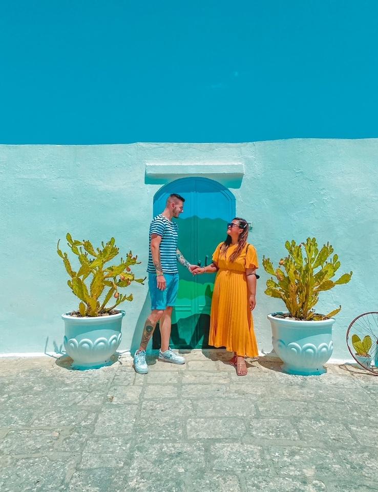 Coppia di innamorati si guarda sorridendo di fronte alla coloratissima porta di Ostuni circondati da due cactus in Puglia