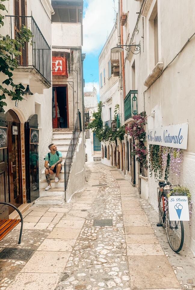Ragazzo seduto sulle scale in un vicolo instagrammabile di Peschici con case bianche