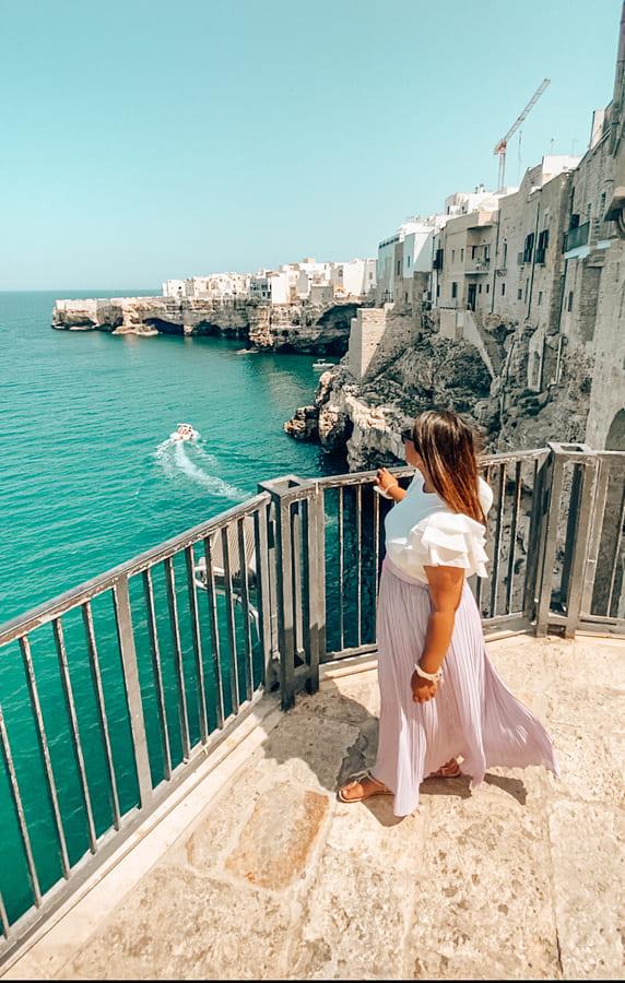 Ragazza guarda l'orizzonte dalla bellissima terrazza panoramica instagrammabile di Polignano sul mare e sulle case bianche
