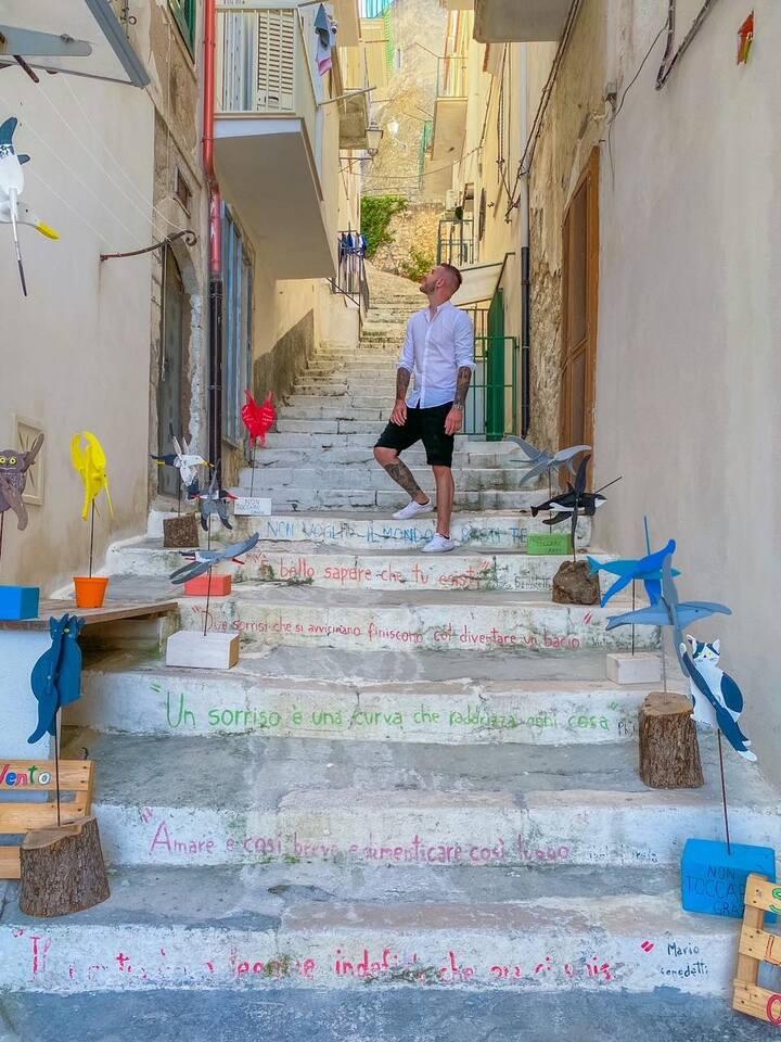 Ragazzo in posa in una scalinata instagrammabile dove fare foto a Vieste