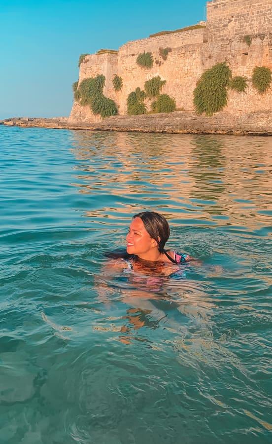 ragazza nuota nel mare della spiaggia di Porto Ghiacciolo a Monopoli durante il tramonto