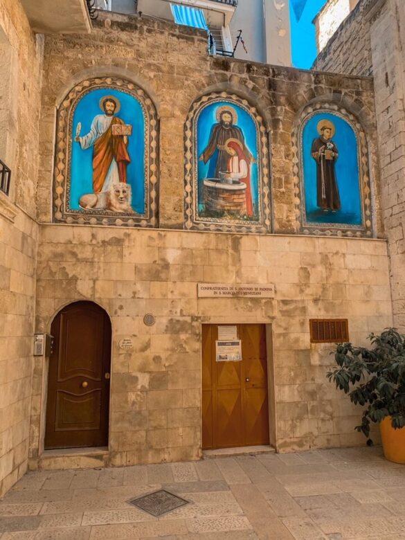 Facciata con tre quadri di tre santi di una chiesa del centro storico di Bari in Puglia