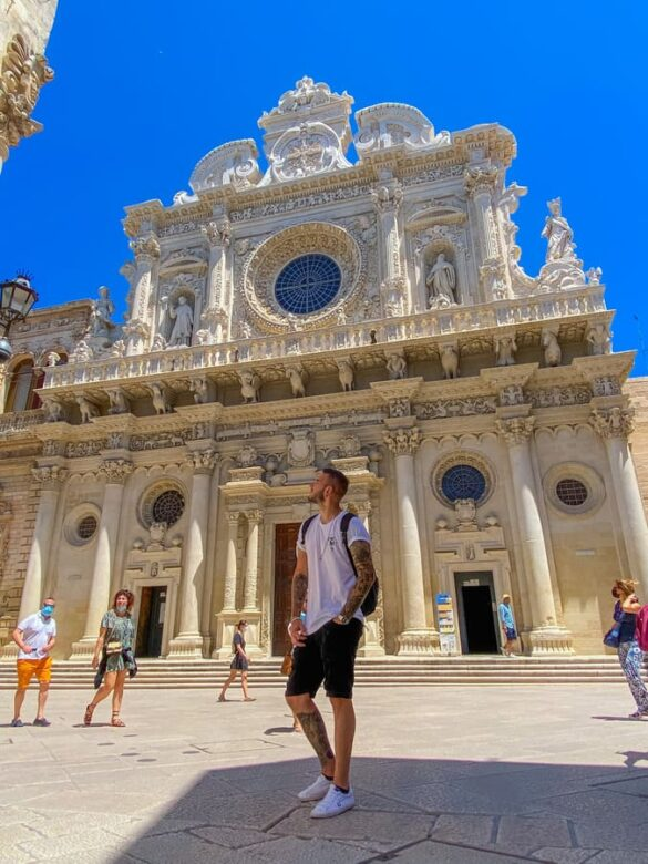 ragazzo guarda con meraviglia la bellissima Basilica di Santa Croce di Lecce in Puglia