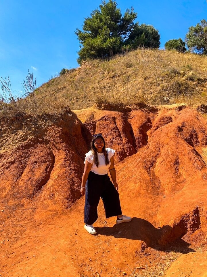 ragazza fa trekking sul terreno rosso della Cava di Bauxite