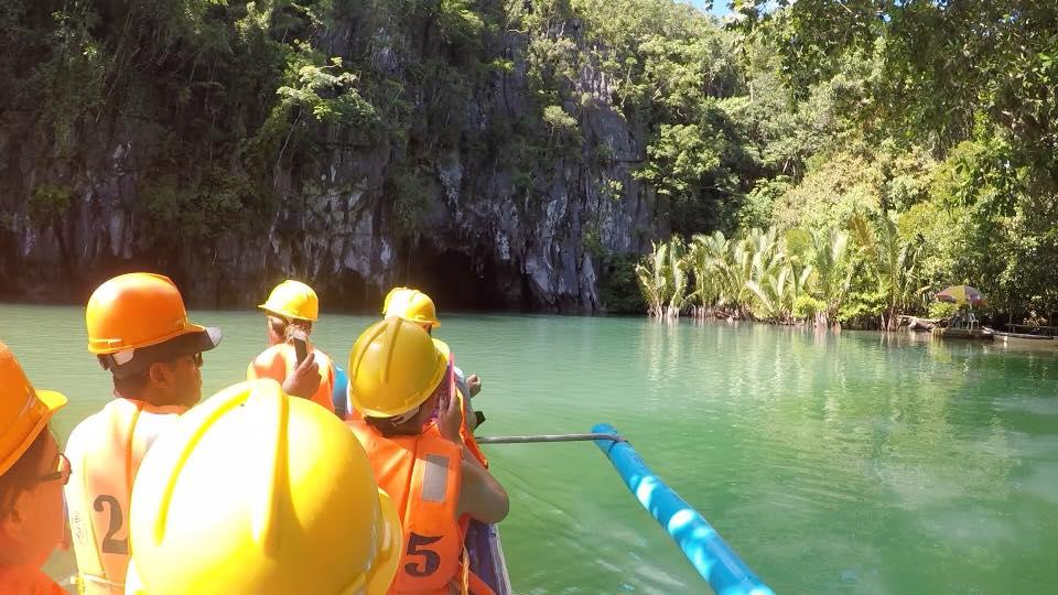 turisti con caschetto sulla barca stanno per entrare nella grotta per visitare il Fiume sotterraneo nelle Filippine