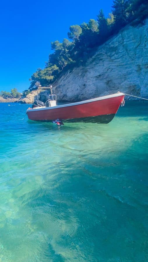 barca che galleggia sull'acqua limpida del mare limpido nel Gargano in Puglia