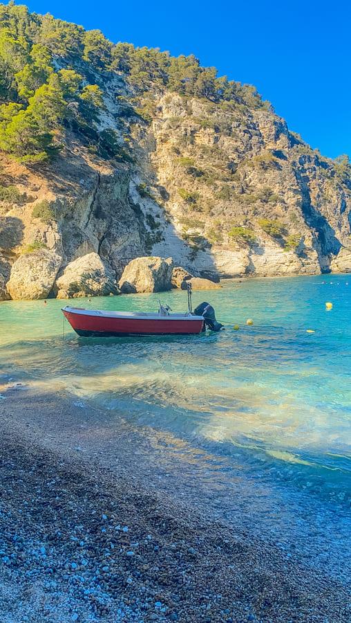 spiaggia costa garganica con acqua limpida e barca in primo piano