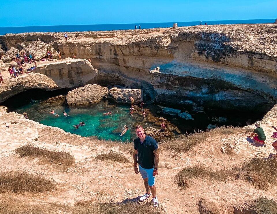 Ragazzo sorride di fronte alla Grotta della Poesia nel Salento in Puglia