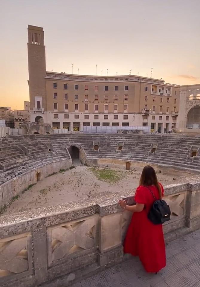 ragazza vestita di rosso ammira il meraviglioso anfiteatro di Lecce in Puglia