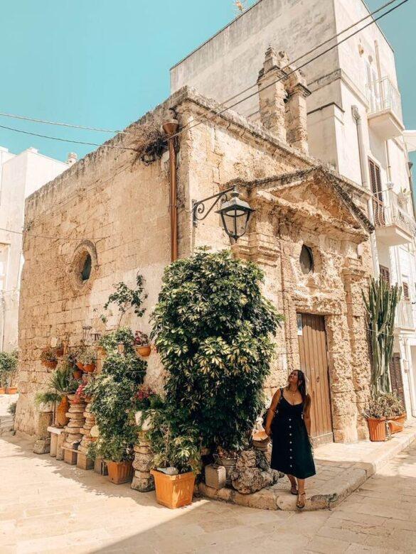Ragazza sorridente di fronte a un bellissimo edificio barocco del centro storico di Monopoli in Puglia
