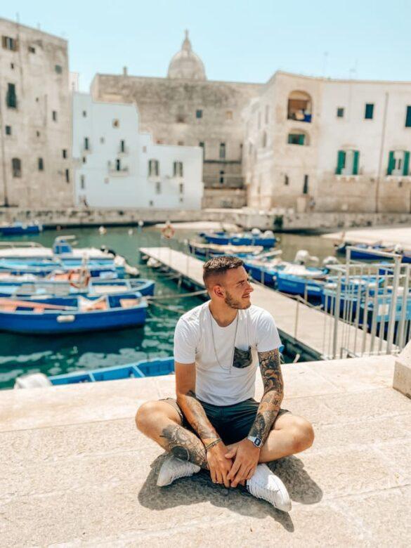 ragazzo ammira il bellissimo porto antico di Monopoli in Puglia