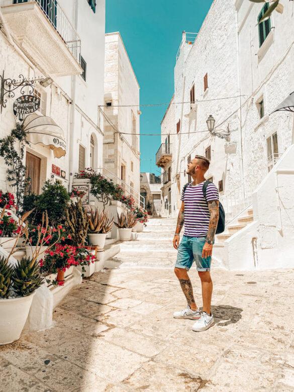 ragazzo ammira il vicolo bianco di Ostuni in Puglia