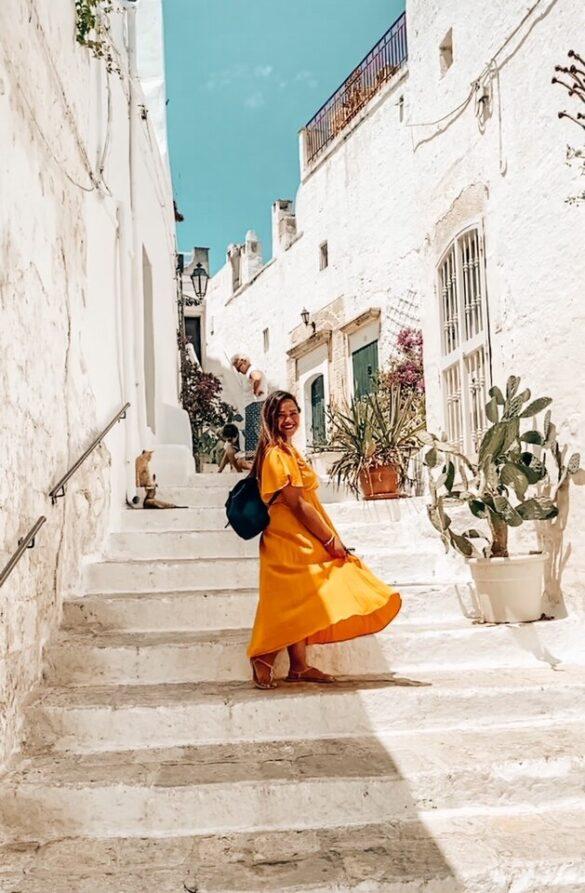 ragazza volteggia sulla scalinata di un vicolo bellissimo ad Ostuni in Puglia