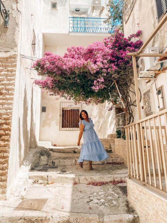 ragazza balla vicolo Peschici con fiori primo giorno itinerario una settimana Puglia