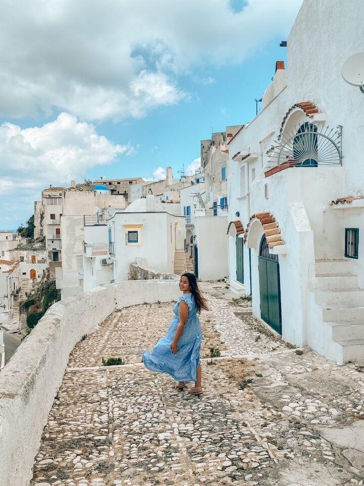 Ragazza cammina nel vicolo più fotografato di Peschici con cupola blu e case greche