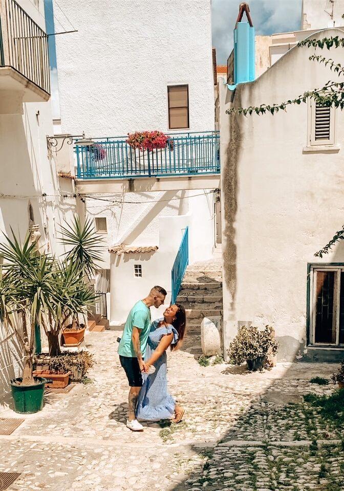 Coppia ride in un Bellissimo vicolo instagrammabile a Peschici con balconate azzurre case e piante