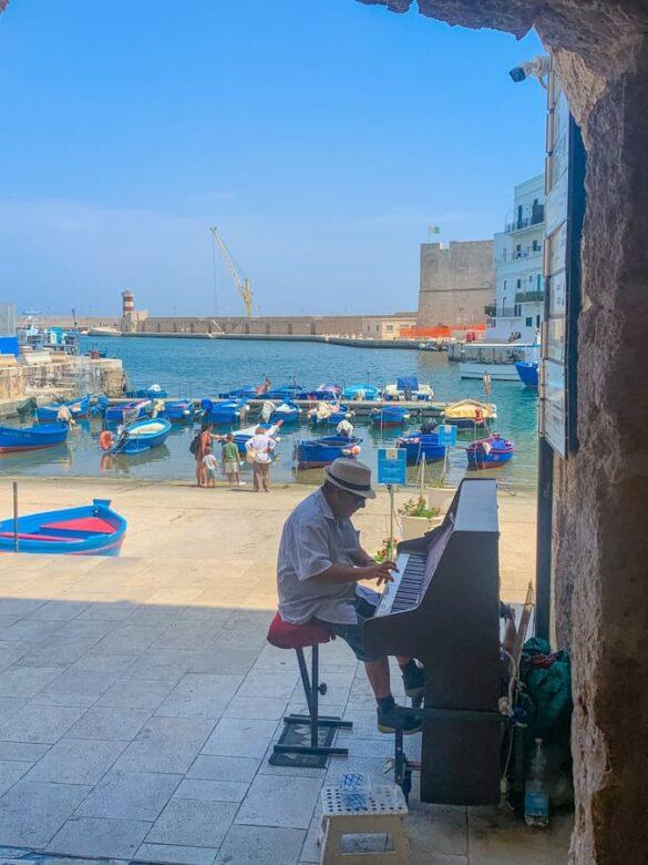Pianista suona il pianoforte di fronte al porto antico di Monopoli in Puglia