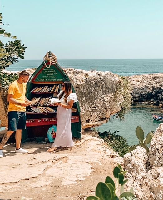 coppia di ragazzi legge libri davanti alla bellissima libreria verde sul mare di Polignano