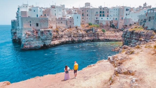 coppia che ammira la vista sulla baia di Polignano a Mare in Puglia, foto scattata dal drone