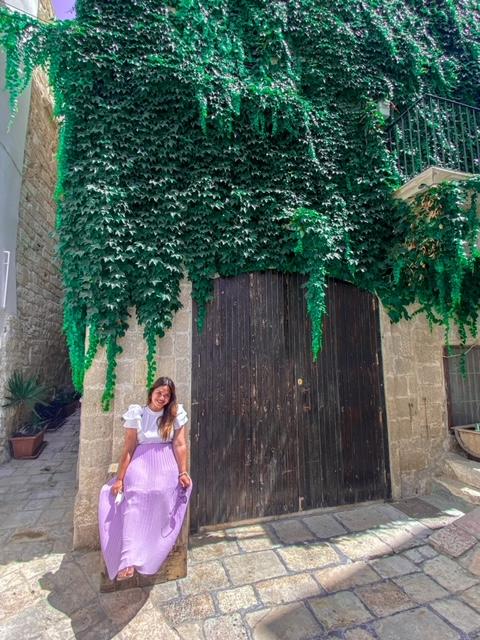 ragazza seduta davanti a una casa instagrammabile di Polignano