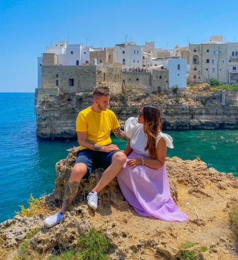 Coppia seduta sulla roccia instagrammabile con vista sulla baia della Lama Monachile per fare una foto instagrammabile