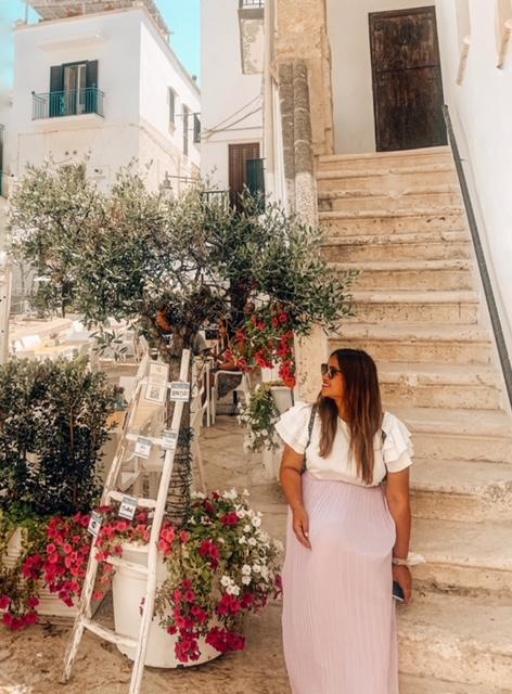 ragazza seduta sulla scalinata instagrammabile con fiori nel centro di Polignano a mare