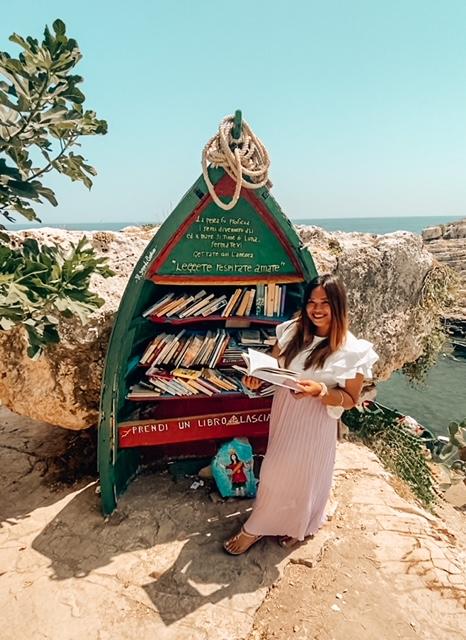 ragazza davanti alla libreria verde instagrammabile di Polignano