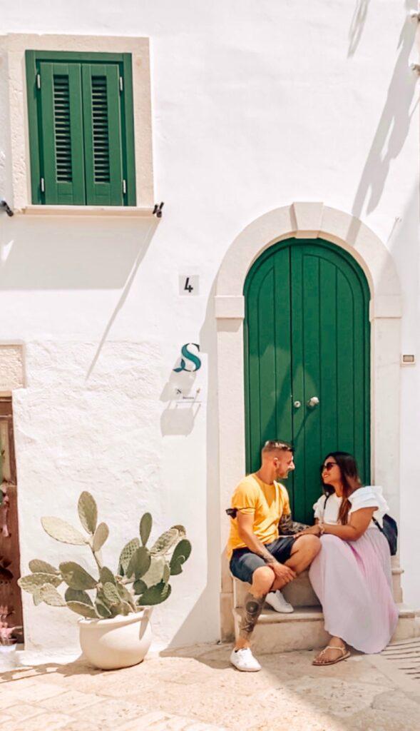 coppia seduta davanti a una porta instagrammabile verde a Polignano