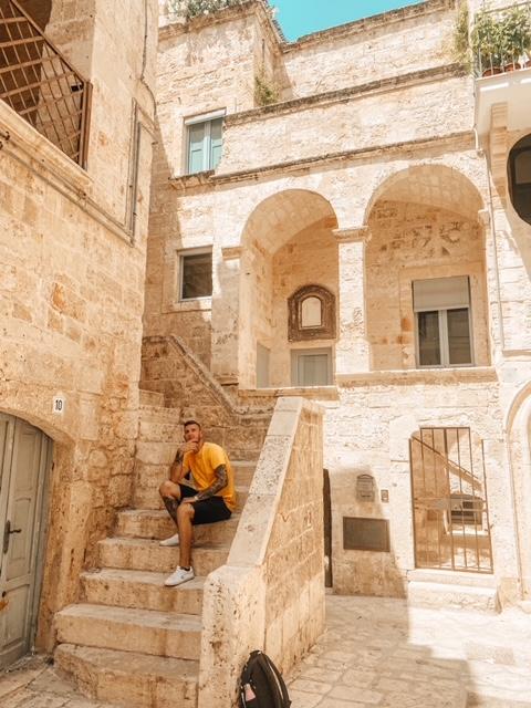ragazzo seduto sulla scalinata dove fare foto a Polignano instagrammabile
