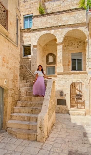 ragazza sorride sulla scalinata instagrammabile beige in un vicolo di Polignano