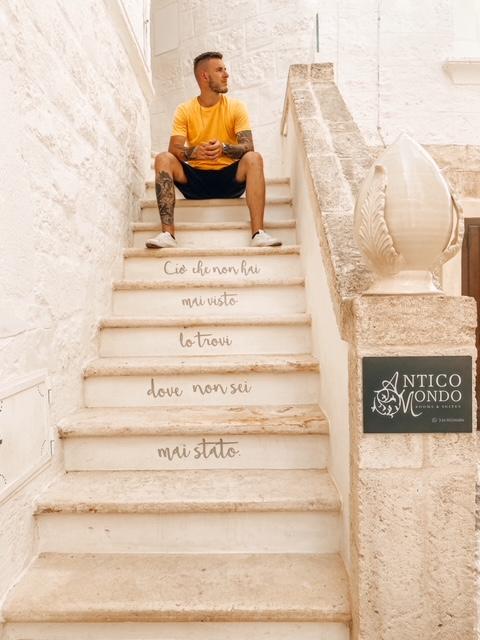 Ragazzo seduto su una scala di una casa nel centro storico di Polignano con poesia scritta sugli scalini