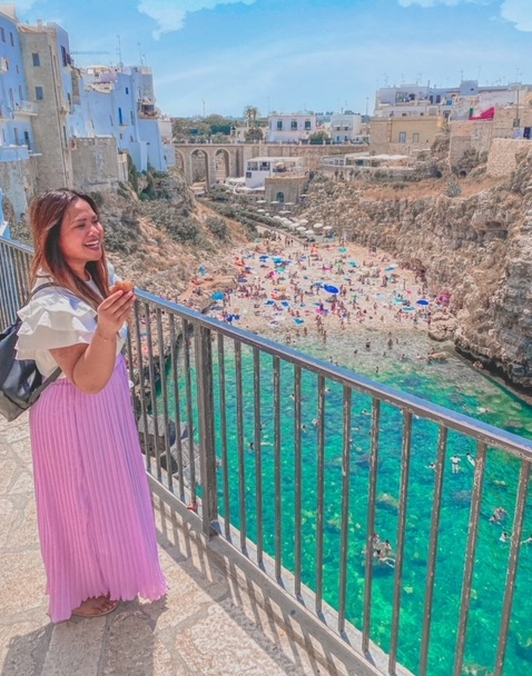 ragazza sorride mangiando un pasticciato sulla terrazza panoramica instagrammabile con vista sulla spiaggia della Lama Monachile