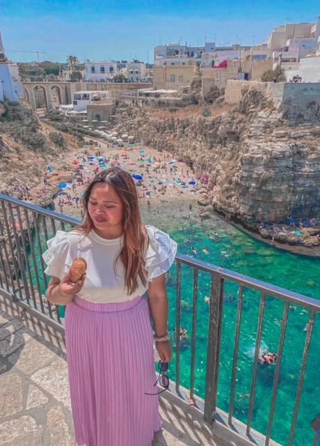 Ragazza sorride con un pasticiotto in mano sulla terrazza panoramica instagrammabile di Polignano