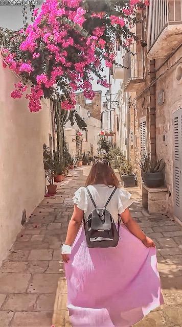 Ragazza cammina in un vicolo instagrammabile pieno di fiori e cactus dove fare foto a Polignano