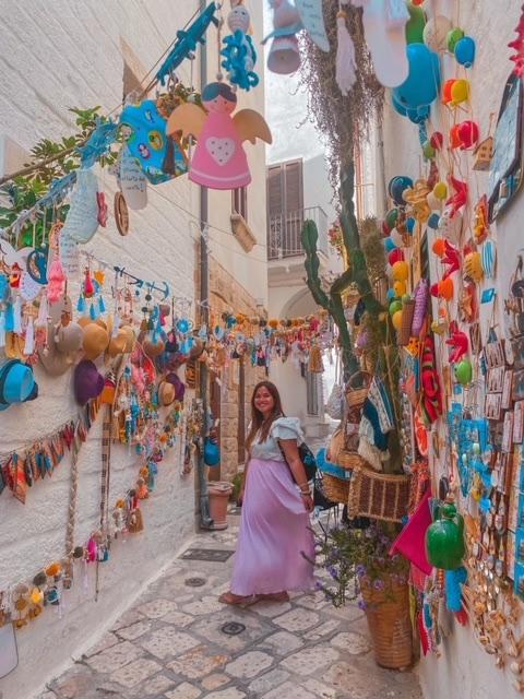 Ragazza cammina in un vicolo pieno di decorazioni instagrammabili dove fare una bellissima foto a Polignano instagrammabile