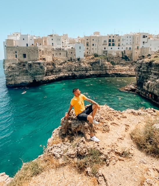 ragazzo seduto sulla roccia di fronte alla baia monachine per fare una foto a Polignano