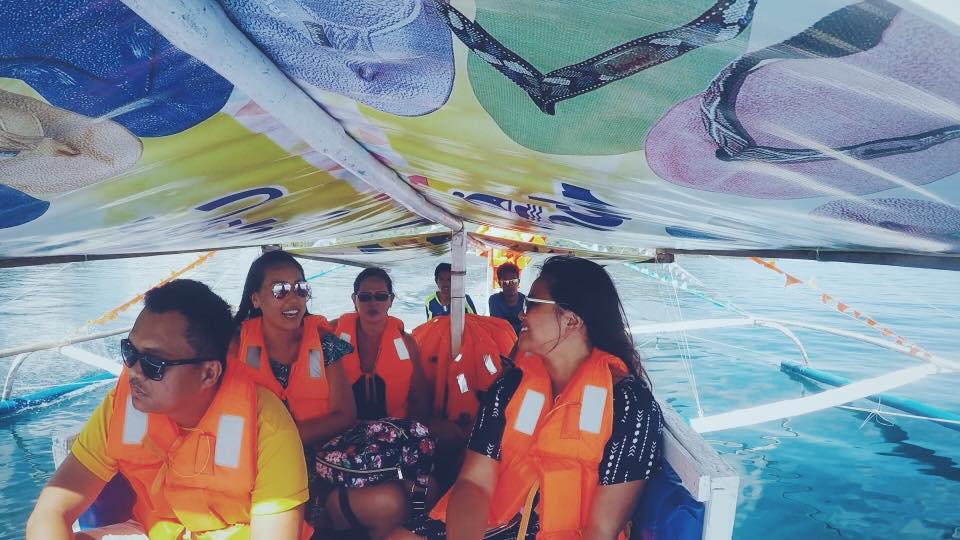 gruppo di turisti sorridono sulla barca che va verso il Fiume sotterraneo nelle Filippine
