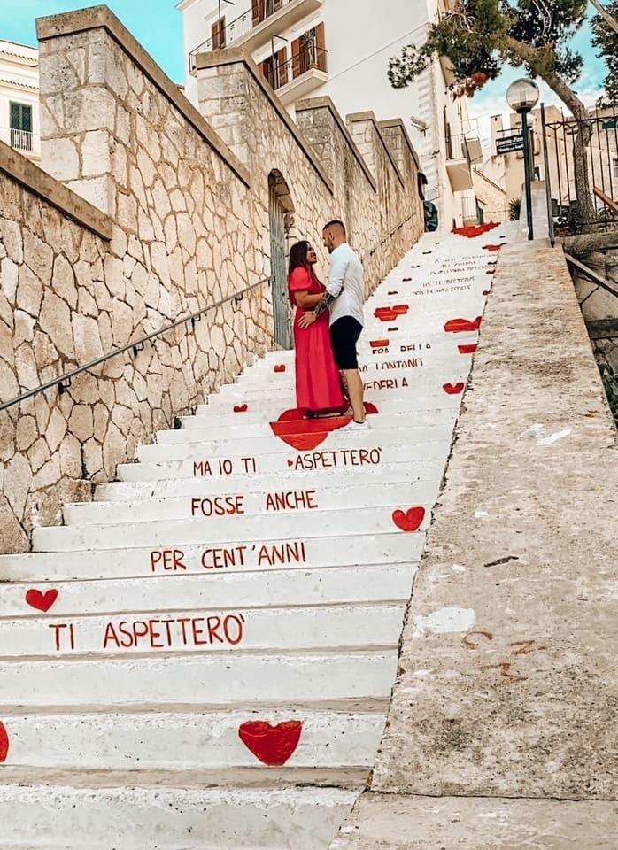 coppia sulla bellissima scalinata dell'amore di Vieste primo giorno itinerario una settimana Puglia