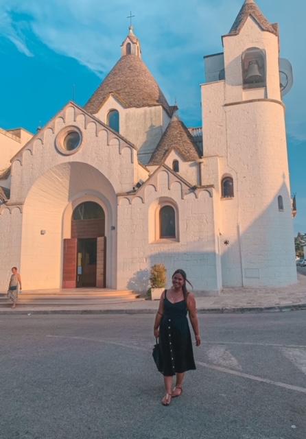 ragazza sorride davanti alla bellissima Parrocchia di Sant'Antonio di Alberobello