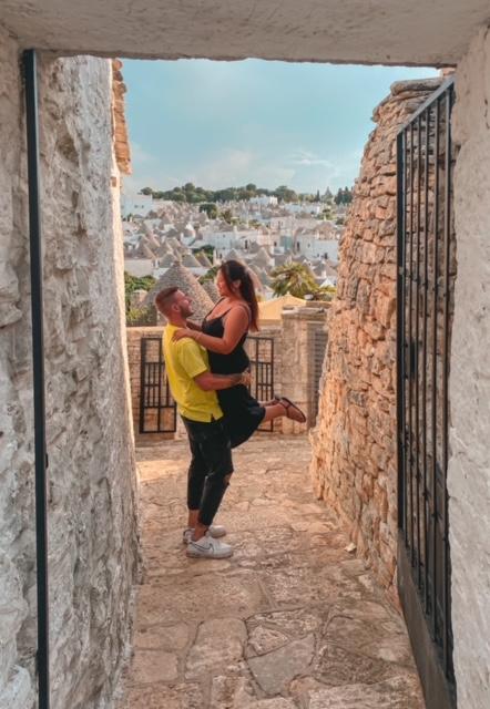 Coppia abbracciata sorride nel punto panoramico da vedere a Alberobello in un giorno